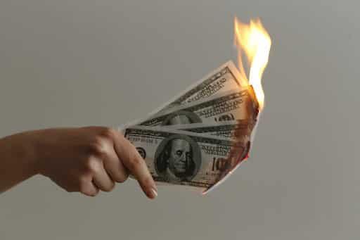Someone holding four, burning, one hundred dollar bills.