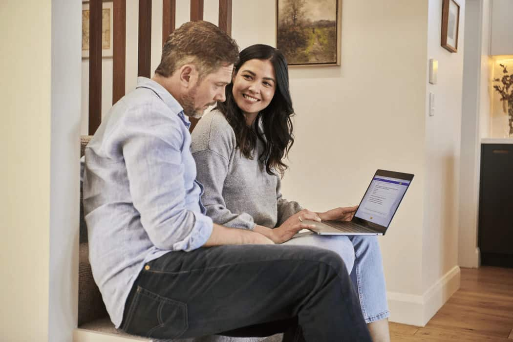 A man and woman sitting together looking at a laptop.