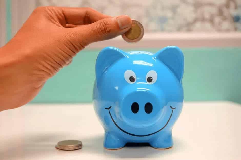 Someone putting money into a small, blue, smiling piggybank.