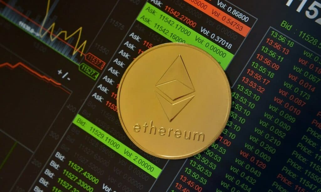 A physical Ethereum cryptocurrency token sitting on top of a screen showing large amounts of crypto exchange data.