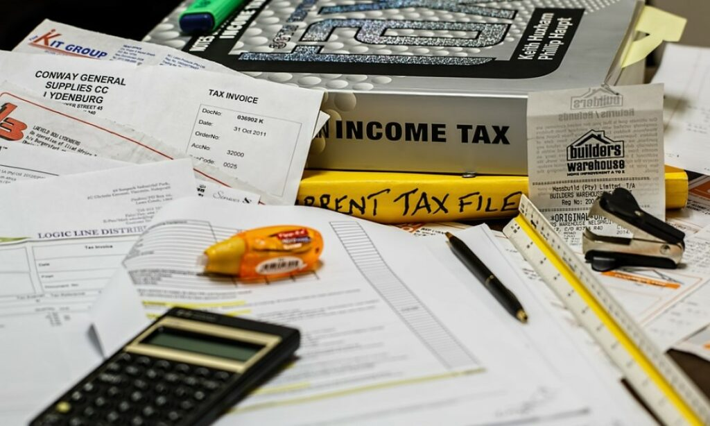 A table full of tax documents, tax books, receipts, and various office supplies.