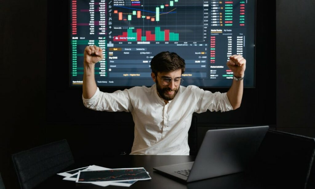 An excited man working with a laptop to exchange cryptocurrencies through DeFi systems without the involvement of unnecessary intermediaries.