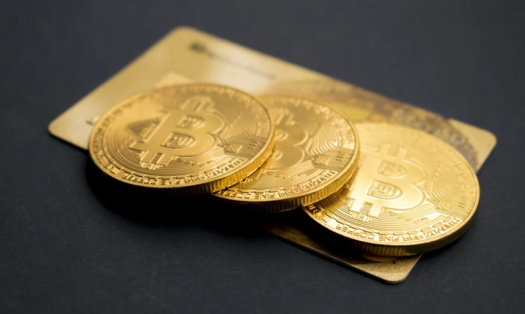 Three gold bitcoins laying on top of a gold credit card.