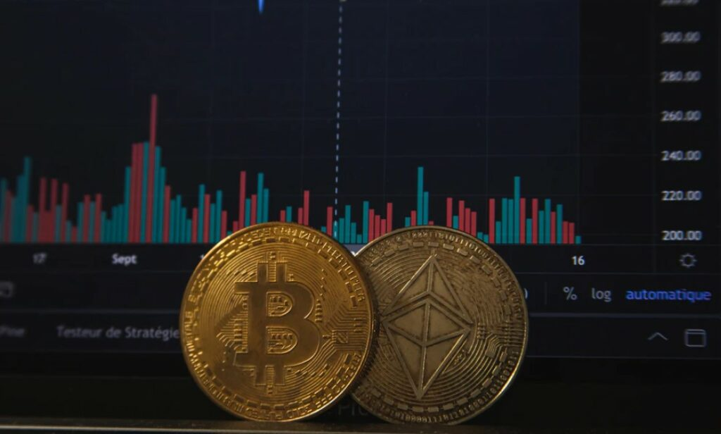 Two gold bitcoins on top of a laptop keyboard, with analytical cryptocurrency data displayed on the screen.